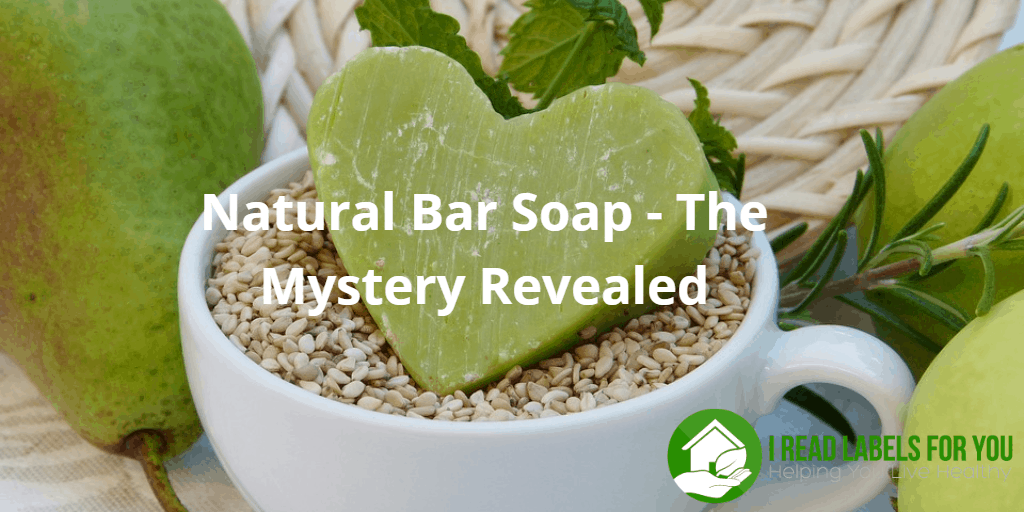 Natural Bar Soap - The Mystery Revealed A photo of a white coffee cup filled with beans. There is a green soap bar on top of the cup and a green pear on the left.