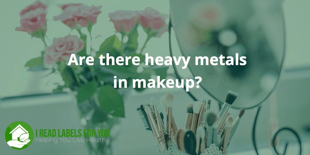 Are there heavy metals in makeup? How do we choose the safest makeup brands? A picture of a mirror, makeup brushes and a vase with roses.