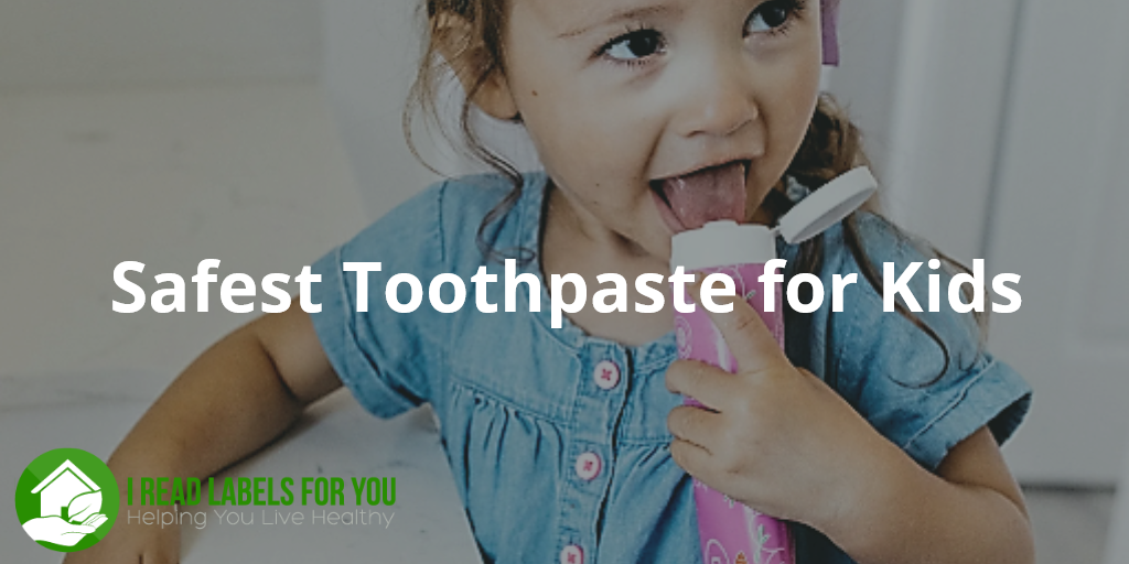 Safest Toothpaste for Kids Dr. Brite. A photo of a little girl holding an open toothpaste tube and licking the paste off the lid.